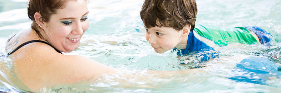 child with swimming instructor