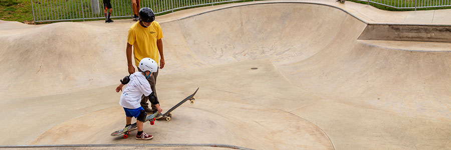 child and instructor at skateboarding lesson