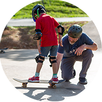 Adult Instructing a Child on Skateboarding